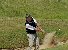 Mike Reynard plays from the bunker on the 8th